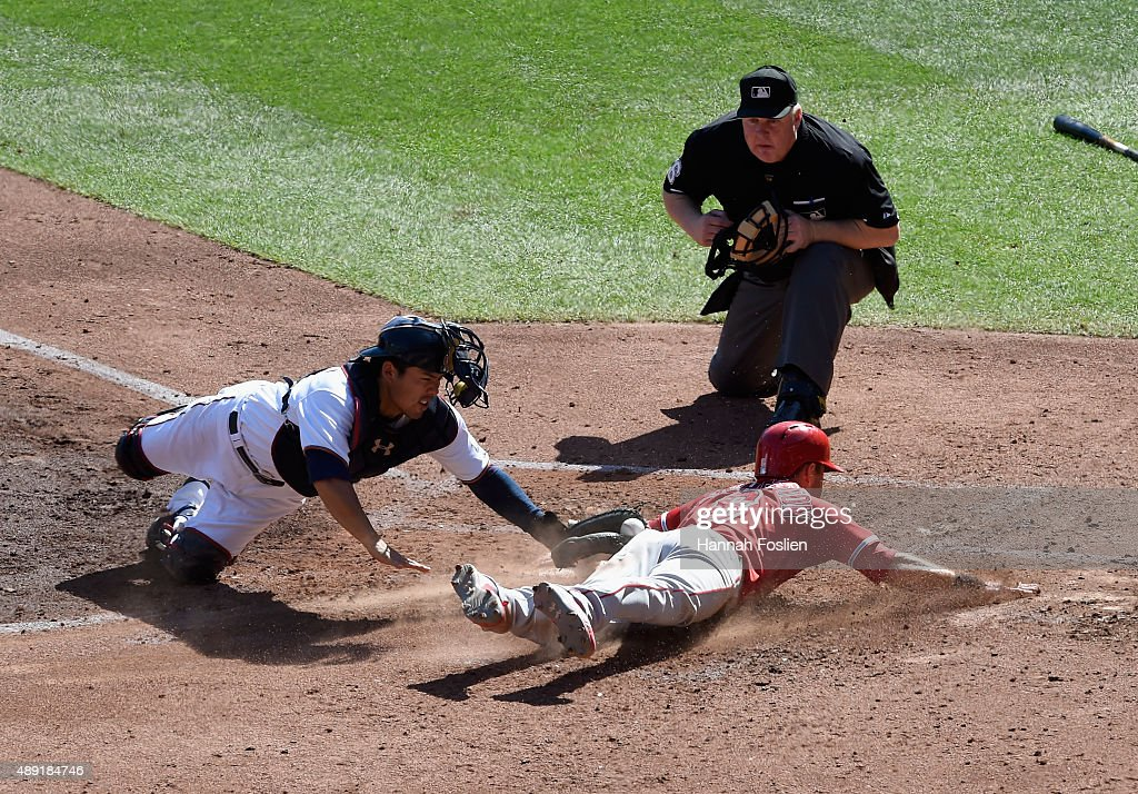 Taylor Featherston of the Los Angeles Angels of Anaheim slides into home plate to score a run as Kurt Suzuki of the Minnesota Twins applies the tag...