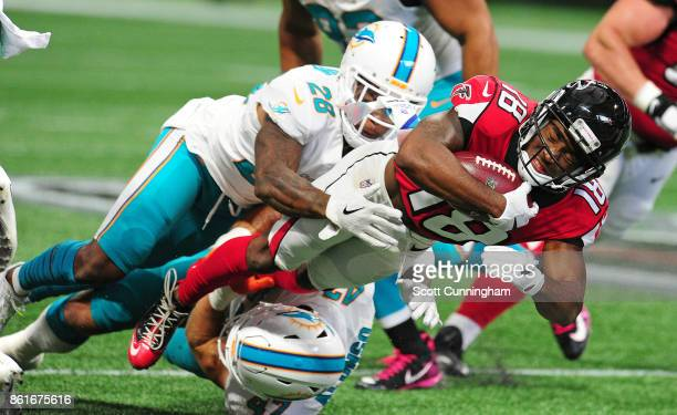 Taylor Gabriel of the Atlanta Falcons is tackled by Damien Williams and Kiko Alonso of the Miami Dolphins at MercedesBenz Stadium on October 15 2017...