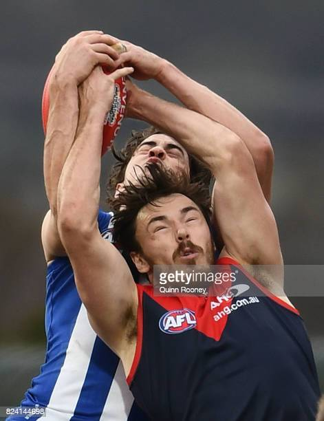 Taylor Garner of the Kangaroos and Michael Hibberd of the Demons compete for a mark during the round 19 AFL match between the North Melbourne...