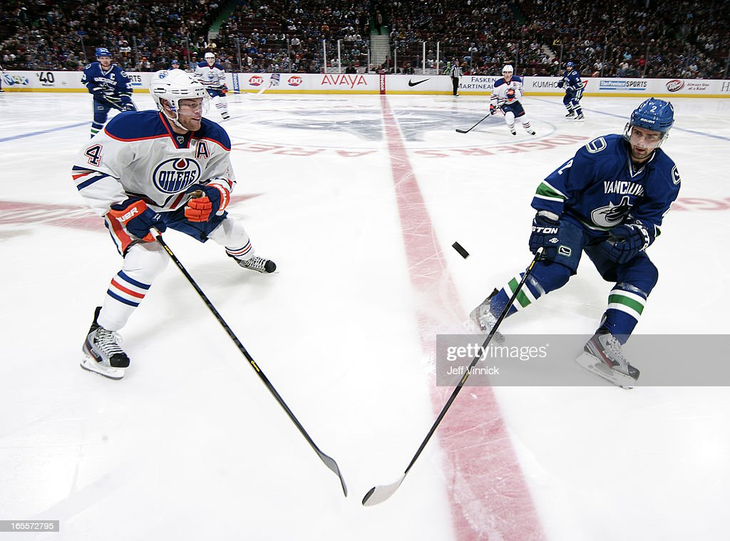 <a gi-track='captionPersonalityLinkClicked' href=/galleries/search?phrase=Taylor+Hall&family=editorial&specificpeople=2808377 ng-click='$event.stopPropagation()'>Taylor Hall</a> #4 of the Edmonton Oilers and <a gi-track='captionPersonalityLinkClicked' href=/galleries/search?phrase=Dan+Hamhuis&family=editorial&specificpeople=204213 ng-click='$event.stopPropagation()'>Dan Hamhuis</a> #2 of the Vancouver Canucks spot the puck during their NHL game at Rogers Arena April 4, 2013 in Vancouver, British Columbia, Canada.