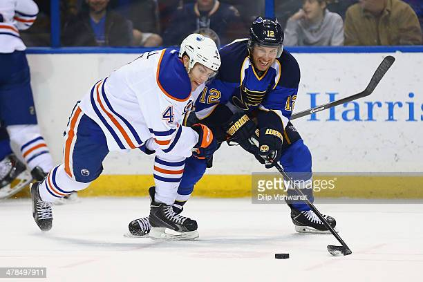 Taylor Hall of the Edmonton Oilers and Derek Roy of the St Louis Blues chase down a loose puck at the Scottrade Center on March 13 2014 in St Louis...