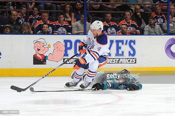 Taylor Hall of the Edmonton Oilers and Karl Stollery of the San Jose Sharks battle for the puck during the game on April 9 2015 at Rexall Place in...
