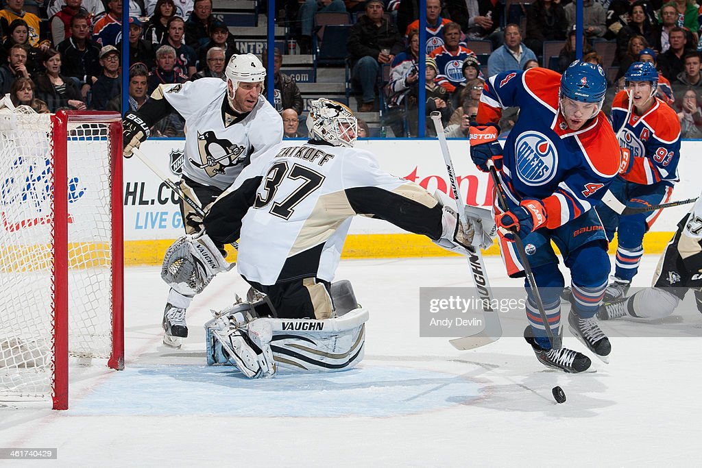 <a gi-track='captionPersonalityLinkClicked' href=/galleries/search?phrase=Taylor+Hall&family=editorial&specificpeople=2808377 ng-click='$event.stopPropagation()'>Taylor Hall</a> #4 of the Edmonton Oilers battles for the puck against <a gi-track='captionPersonalityLinkClicked' href=/galleries/search?phrase=Jeff+Zatkoff&family=editorial&specificpeople=1985171 ng-click='$event.stopPropagation()'>Jeff Zatkoff</a> #37 of the Pittsburgh Penguins on January 10, 2014 at Rexall Place in Edmonton, Alberta, Canada.