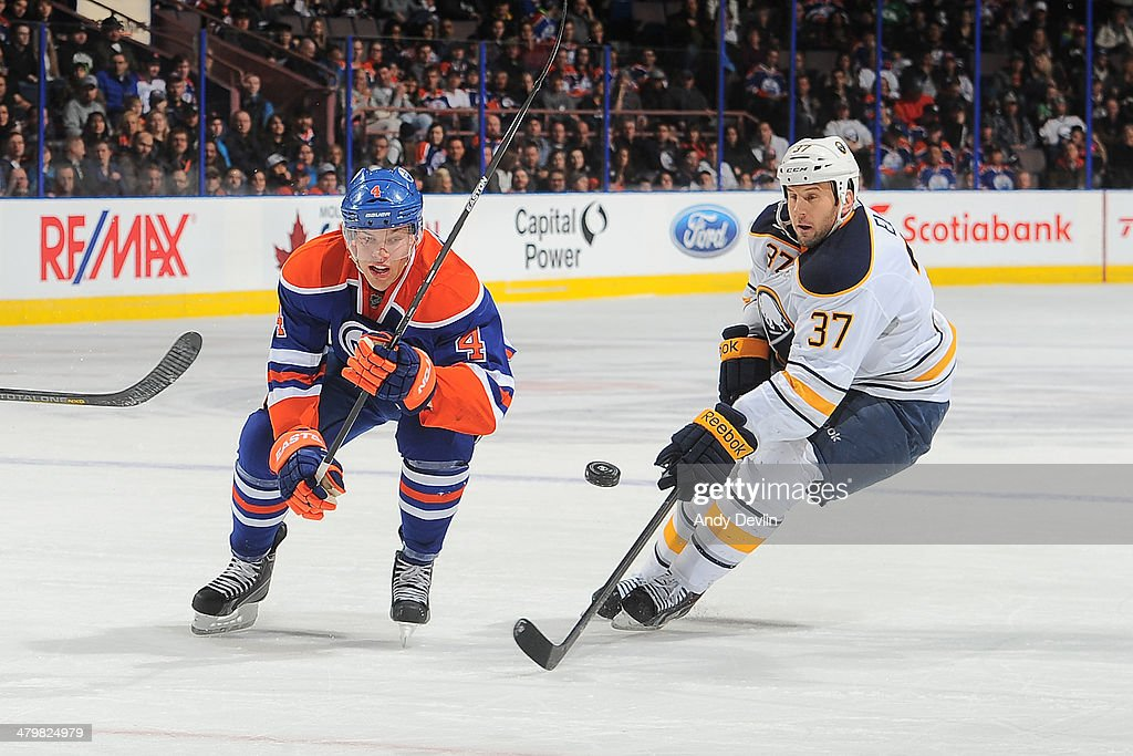 Taylor Hall #4 of the Edmonton Oilers battles for the puck against Matt Ellis #37 of the Buffalo Sabres on March 20, 2014 at Rexall Place in Edmonton, Alberta, Canada.