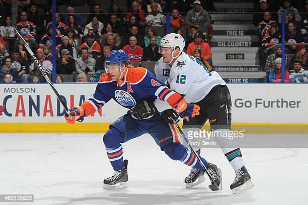 Taylor Hall of the Edmonton Oilers battles for the puck against Patrick Marleau of the San Jose Sharks on December 7 2014 at Rexall Place in Edmonton...