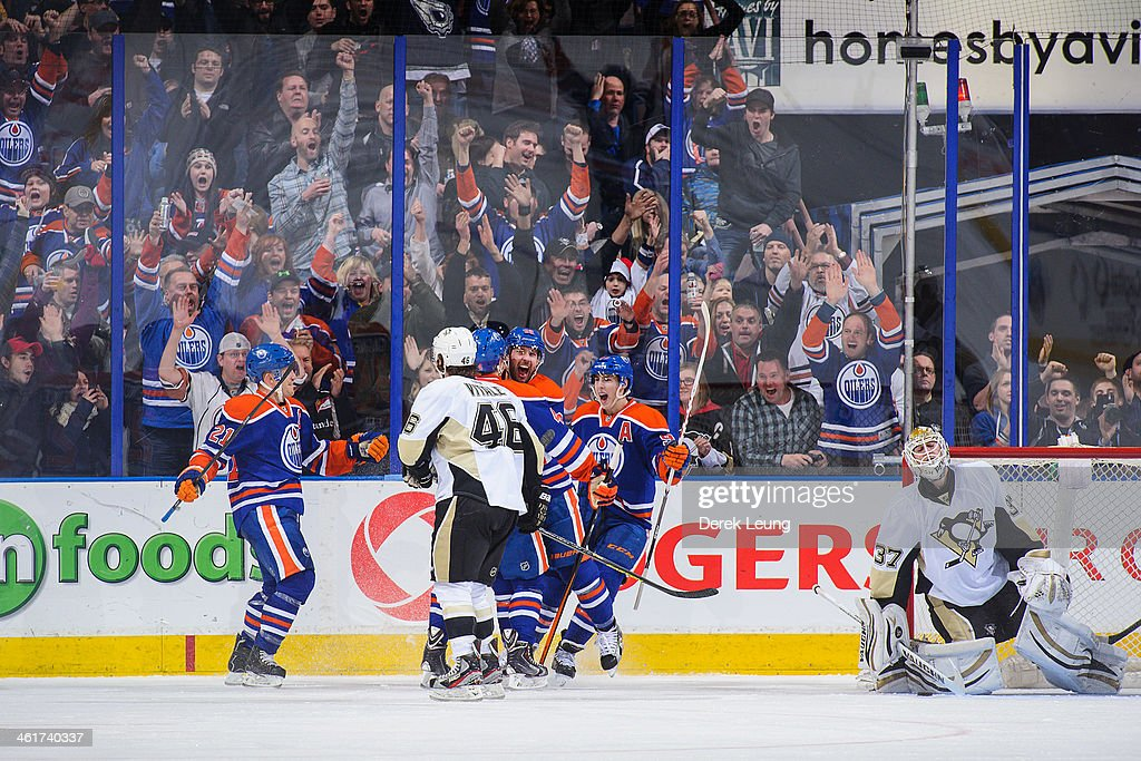 <a gi-track='captionPersonalityLinkClicked' href=/galleries/search?phrase=Taylor+Hall&family=editorial&specificpeople=2808377 ng-click='$event.stopPropagation()'>Taylor Hall</a> #4 (C) of the Edmonton Oilers celebrates scoring his team's second goal against the Pittsburgh Penguins along with his teammates <a gi-track='captionPersonalityLinkClicked' href=/galleries/search?phrase=Andrew+Ference&family=editorial&specificpeople=202264 ng-click='$event.stopPropagation()'>Andrew Ference</a> #21 (L), <a gi-track='captionPersonalityLinkClicked' href=/galleries/search?phrase=Sam+Gagner&family=editorial&specificpeople=4042961 ng-click='$event.stopPropagation()'>Sam Gagner</a> #89 and <a gi-track='captionPersonalityLinkClicked' href=/galleries/search?phrase=Ryan+Nugent-Hopkins&family=editorial&specificpeople=7144190 ng-click='$event.stopPropagation()'>Ryan Nugent-Hopkins</a> #93 (R) during an NHL game at Rexall Place on January 10, 2014 in Edmonton, Alberta, Canada. The Oilers won 4-3 in overtime.