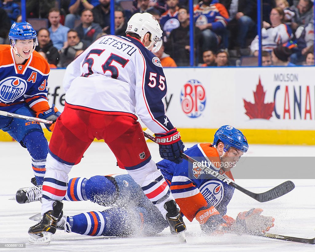 <a gi-track='captionPersonalityLinkClicked' href=/galleries/search?phrase=Taylor+Hall&family=editorial&specificpeople=2808377 ng-click='$event.stopPropagation()'>Taylor Hall</a> #4 of the Edmonton Oilers gets knocked off his feet by <a gi-track='captionPersonalityLinkClicked' href=/galleries/search?phrase=Mark+Letestu&family=editorial&specificpeople=4601071 ng-click='$event.stopPropagation()'>Mark Letestu</a> #55 of the Columbus Blue Jackets during an NHL game at Rexall Place on November 19, 2013 in Edmonton, Alberta, Canada.