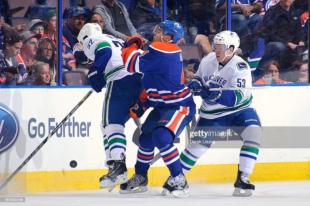 <a gi-track='captionPersonalityLinkClicked' href=/galleries/search?phrase=Taylor+Hall&family=editorial&specificpeople=2808377 ng-click='$event.stopPropagation()'>Taylor Hall</a> #4 of the Edmonton Oilers gets sandwiched between <a gi-track='captionPersonalityLinkClicked' href=/galleries/search?phrase=Dale+Weise&family=editorial&specificpeople=5527418 ng-click='$event.stopPropagation()'>Dale Weise</a> #32 and <a gi-track='captionPersonalityLinkClicked' href=/galleries/search?phrase=Bo+Horvat&family=editorial&specificpeople=8321784 ng-click='$event.stopPropagation()'>Bo Horvat</a> #53 of the Vancouver Canucks during a preseason NHL game at Rexall Place on September 21, 2013 in Edmonton, Alberta, Canada.