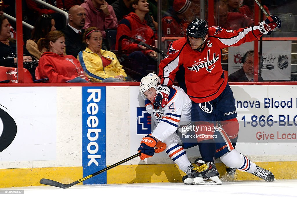 <a gi-track='captionPersonalityLinkClicked' href=/galleries/search?phrase=Taylor+Hall&family=editorial&specificpeople=2808377 ng-click='$event.stopPropagation()'>Taylor Hall</a> #4 of the Edmonton Oilers is checked into the boards by Alex Ovechkin #8 of the Washington Capitals in the second period during an NHL game at Verizon Center on October 14, 2013 in Washington, DC.