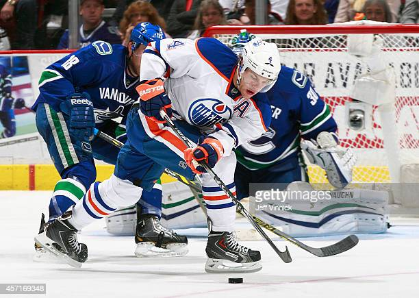 Taylor Hall of the Edmonton Oilers looks for a loose puck during their NHL game against the Vancouver Canucks at Rogers Arena October 11 2014 in...
