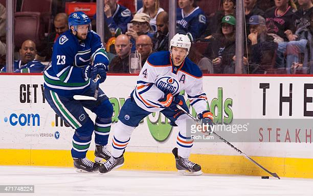 Taylor Hall of the Edmonton Oilers looks to make a pass while pressured by Alexander Edler of the Vancouver Canucks in NHL action on April 2015 at...