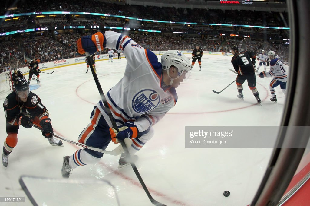 <a gi-track='captionPersonalityLinkClicked' href=/galleries/search?phrase=Taylor+Hall&family=editorial&specificpeople=2808377 ng-click='$event.stopPropagation()'>Taylor Hall</a> #4 of the Edmonton Oilers plays the puck along the corner boards as <a gi-track='captionPersonalityLinkClicked' href=/galleries/search?phrase=Saku+Koivu&family=editorial&specificpeople=202253 ng-click='$event.stopPropagation()'>Saku Koivu</a> #11 of the Anaheim Ducks hooks Hall's stick in the second period during the NHL game at Honda Center on April 8, 2013 in Anaheim, California. The Ducks defeated the Oilers 2-1.