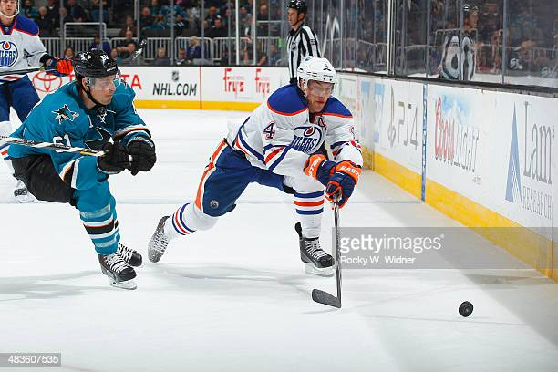 Taylor Hall of the Edmonton Oilers skates after the puck against Justin Braun of the San Jose Sharks at SAP Center on April 1 2014 in San Jose...