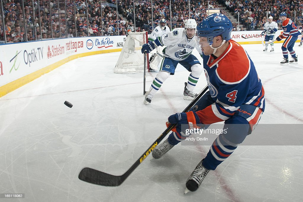<a gi-track='captionPersonalityLinkClicked' href=/galleries/search?phrase=Taylor+Hall&family=editorial&specificpeople=2808377 ng-click='$event.stopPropagation()'>Taylor Hall</a> #4 of the Edmonton Oilers skates for the puck against <a gi-track='captionPersonalityLinkClicked' href=/galleries/search?phrase=Dan+Hamhuis&family=editorial&specificpeople=204213 ng-click='$event.stopPropagation()'>Dan Hamhuis</a> #2 of the Vancouver Canucks on March 30, 2013 at Rexall Place in Edmonton, Alberta, Canada.
