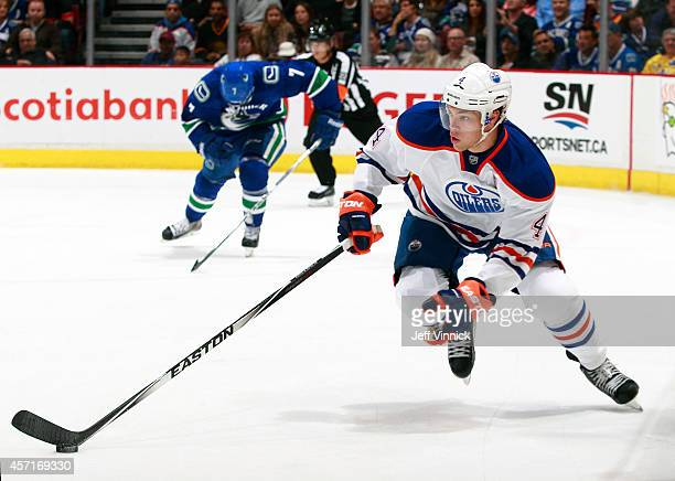 Taylor Hall of the Edmonton Oilers skates up ice with the puck during their NHL game against the Vancouver Canucks at Rogers Arena October 11 2014 in...