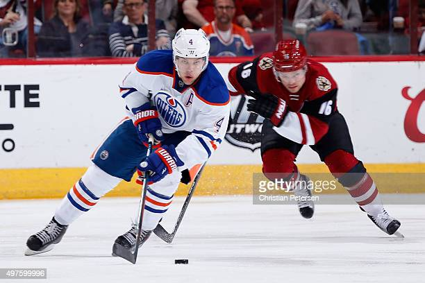 Taylor Hall of the Edmonton Oilers skates with the puck past Max Domi of the Arizona Coyotes during the NHL game at Gila River Arena on November 12...