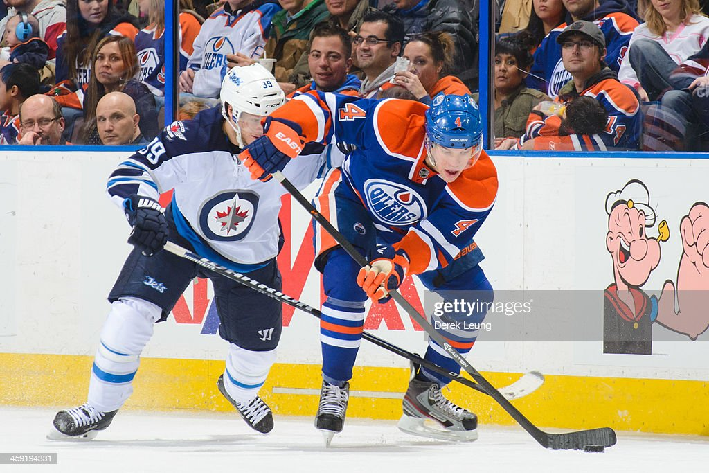 <a gi-track='captionPersonalityLinkClicked' href=/galleries/search?phrase=Taylor+Hall&family=editorial&specificpeople=2808377 ng-click='$event.stopPropagation()'>Taylor Hall</a> #4 of the Edmonton Oilers skates with the puck past <a gi-track='captionPersonalityLinkClicked' href=/galleries/search?phrase=Tobias+Enstrom&family=editorial&specificpeople=2538468 ng-click='$event.stopPropagation()'>Tobias Enstrom</a> #39of the Winnipeg Jets during an NHL game at Rexall Place on December 23, 2013 in Edmonton, Alberta, Canada. The Oilers defeated the Jets 6-2.