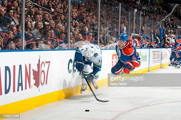 Taylor Hall of the Edmonton Oilers soars through the air trying to get the puck against Keith Ballard of the Vancouver Canucks at Rexall Place on...