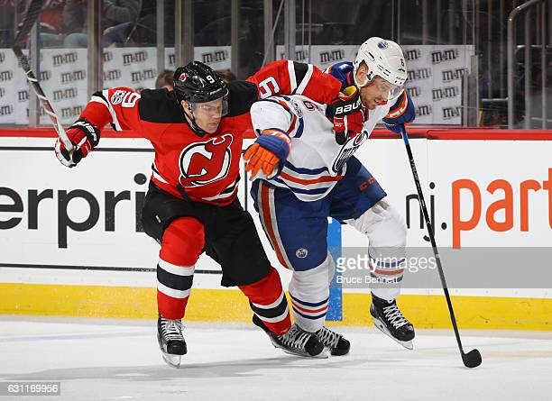 Taylor Hall of the New Jersey Devils and Adam Larsson of the Edmonton Oilers pursue the puck during the second period at the Prudential Center on...
