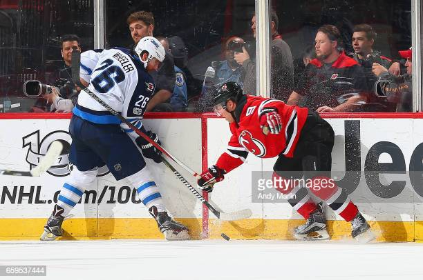 Taylor Hall of the New Jersey Devils and Blake Wheeler of the Winnipeg Jets battle for a loose puck during the game at Prudential Center on March 28...