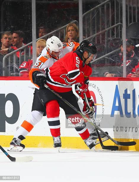 Taylor Hall # of the New Jersey Devils and Valtteri Filppula of the Philadelphia Flyers battle for control of the puck along the boards during the...