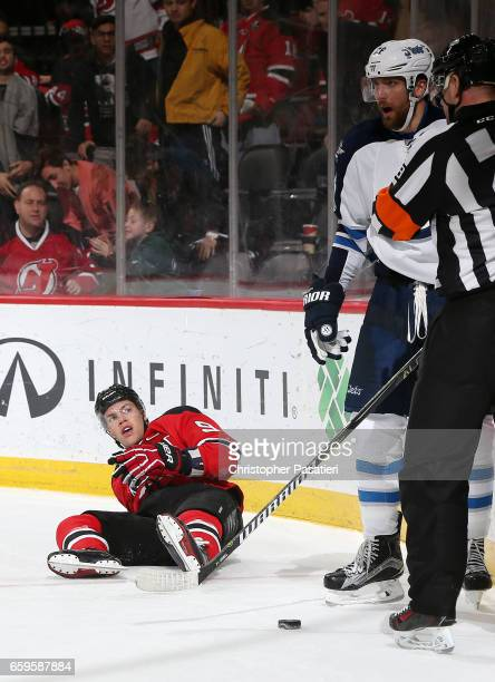 Taylor Hall of the New Jersey Devils looks up after being tripped by Blake Wheeler of the Winnipeg Jets during the overtime period on March 28 2017...