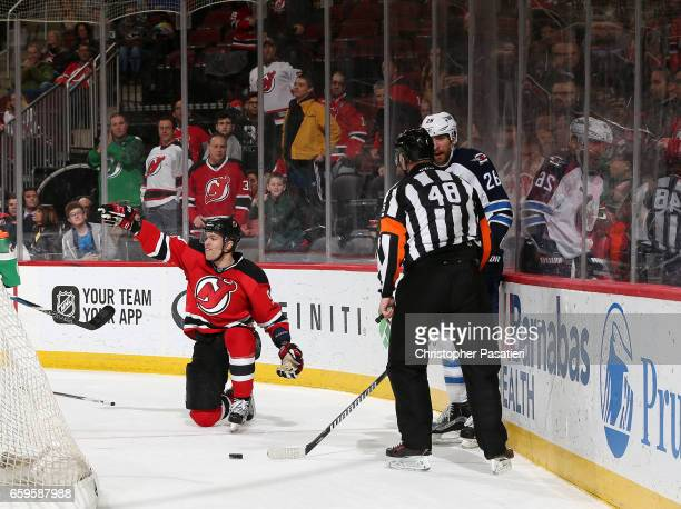 Taylor Hall of the New Jersey Devils reacts after being tripped by Blake Wheeler of the Winnipeg Jets during the overtime period on March 28 2017 at...