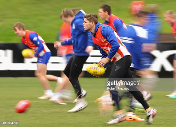 Taylor Hine runs with teammates during a North Melbourne Kangaroos AFL training session at Arden Street Ground on July 9 2014 in Melbourne Australia