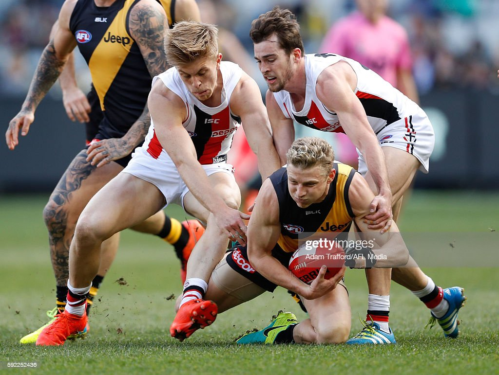Taylor Hunt of the Tigers is tackled by Sebastian Ross and Daniel McKenzie of the Saints during the 2016 AFL Round 22 match between the Richmond...