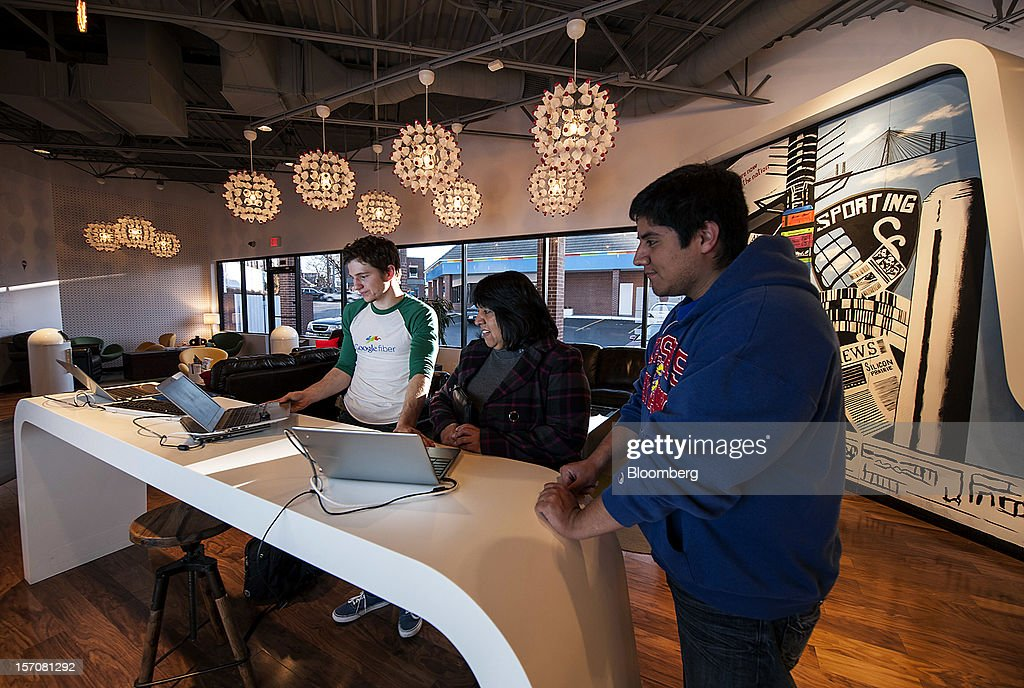 Taylor Kelly, a Google Inc. Fiber Space team member, left, discusses installation plans with customer Anna Rios, center, and her son Jacob Gomez in the showroom of the Fiber Space office in Kansas City, Missouri, U.S., on Tuesday, Nov. 27, 2012. Google Inc. will move a step closer to offering the fastest citywide Internet service in the U.S. when it picks the first neighborhoods in Kansas City to get hooked into a new fiber-optic network. Photographer: Julie Denesha/Bloomberg via Getty Images
