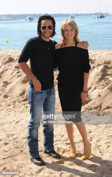 Taylor Kitsch and Malin Akerman during a photocall for the film The Bang Bang Club on the Gray D'Albion beach in Cannes France as part of the 62nd...