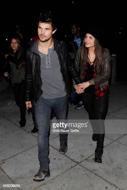 Taylor Lautner and Marie Avgeropoulos are seen arriving at Staples Center on December 09 2013 in Los Angeles California