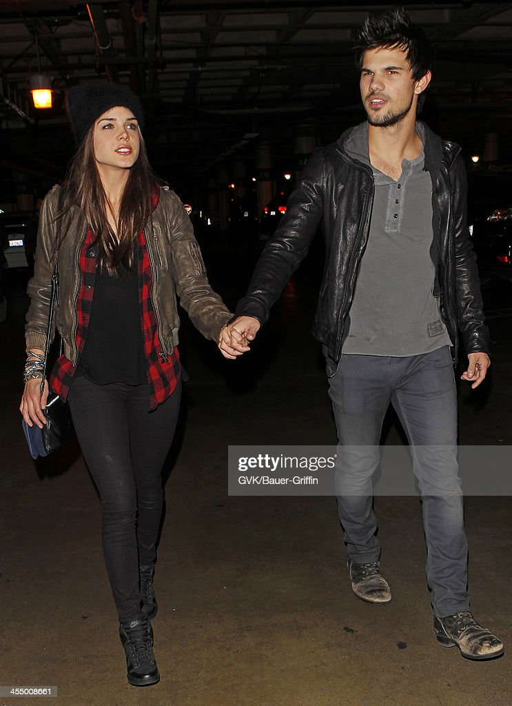 Taylor Lautner and Marie Avgeropoulos are seen arriving at Staples Center on December 09, 2013 in Los Angeles, California.