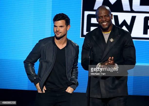 Taylor Lautner and Terry Crews speak onstage at the 2015 American Music Awards at Microsoft Theater on November 22 2015 in Los Angeles California