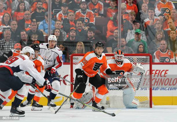 Taylor Leier and Ivan Provorov of the Philadelphia Flyers attempt to break up a pass in front of goaltender Brian Elliott by Nicklas Backstrom and...