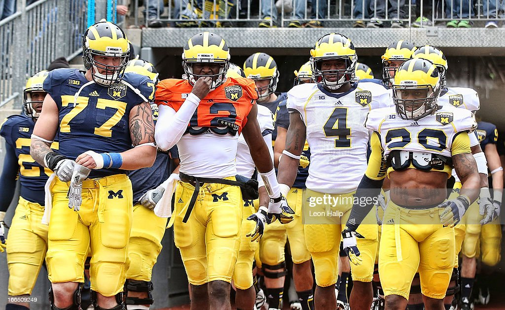 Taylor Lewan #77, Devin Gardner #12, Cameron Gordon #4 and Thomas Gordon #30 of the Michigan Wolverines enter the stadium prior to the start of the annual Spring Game at Michigan Stadium on April 13, 2013 in Ann Arbor, Michigan.