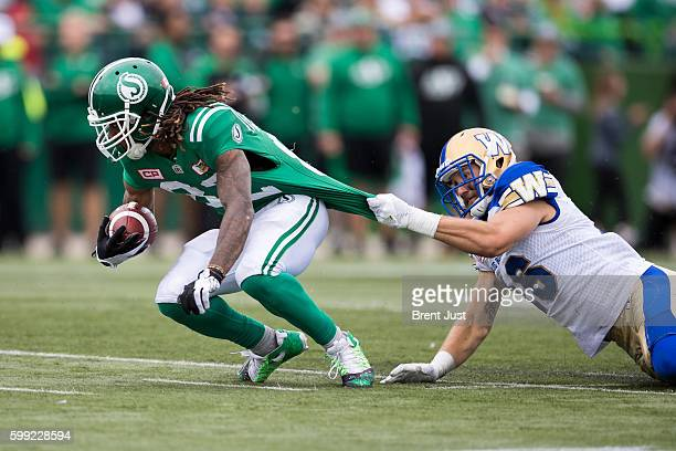 Taylor Loffler of the Winnipeg Blue Bombers grabs the jersey of Naaman Roosevelt of the Saskatchewan Roughriders trying to make a tackle in the game...