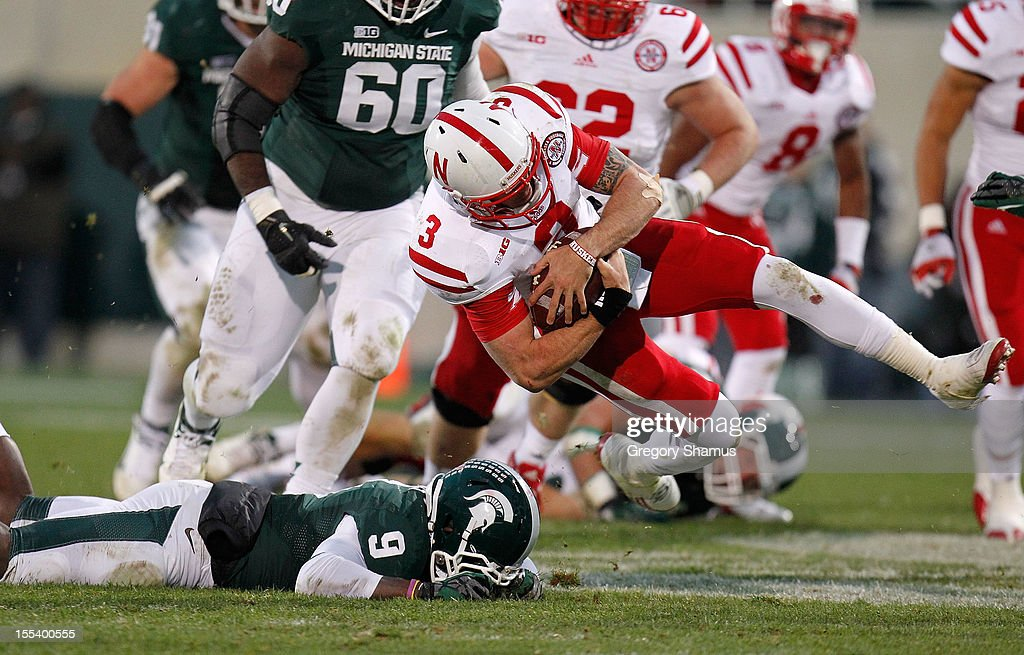 Taylor Martinez #3 of the Nebraska Cornhuskers gets tackled during a fourth quarter run by Isaiah Lewis #9 of the Michigan State Spartans at Spartan Stadium Stadium on November 3, 2012 in East Lansing, Michigan. Nebraska won the game 28-24.