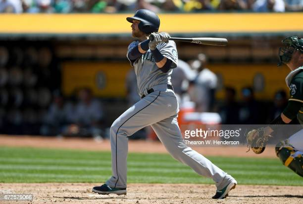 Taylor Motter of the Seattle Mariners swings and watches the flight of his ball as he hits a grand slam home run against the Oakland Athletics in the...