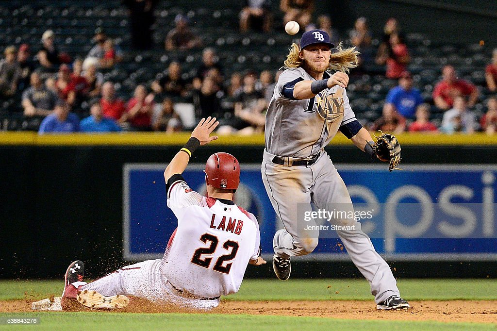 Taylor Motter of the Tampa Bay Rays turns the double play over the sliding Jake Lamb of the Arizona Diamondbacks in the ninth inning at Chase Field...