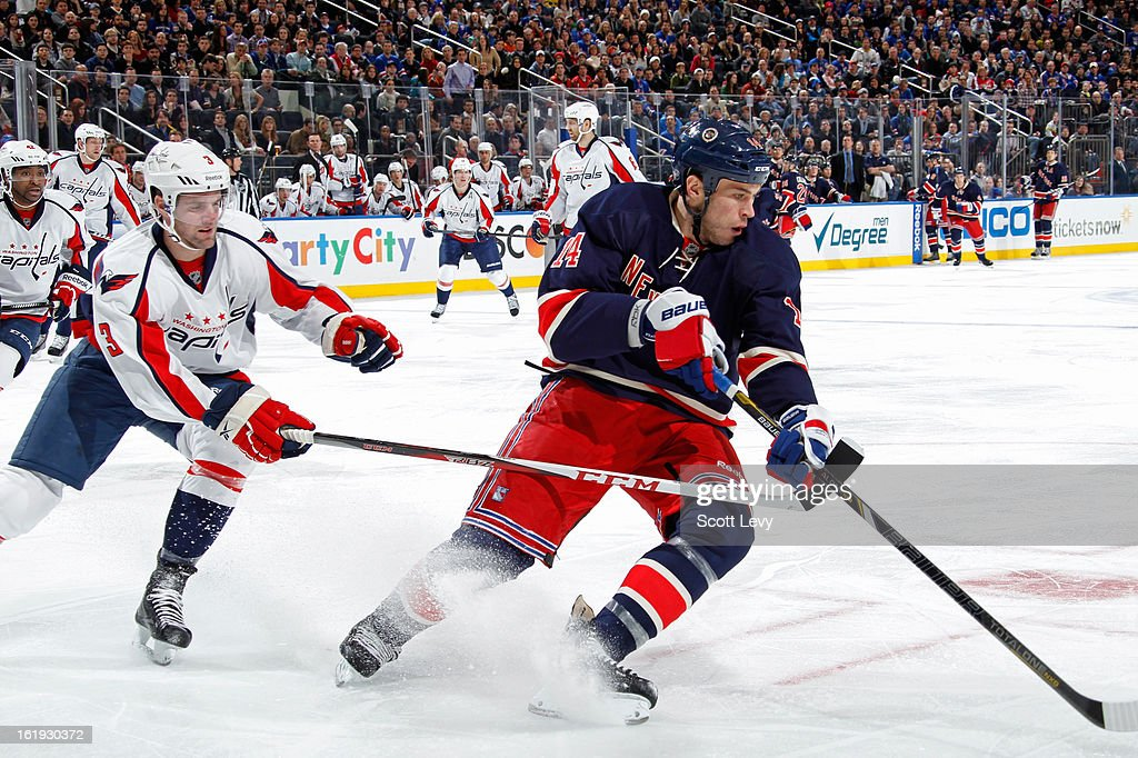 <a gi-track='captionPersonalityLinkClicked' href=/galleries/search?phrase=Taylor+Pyatt&family=editorial&specificpeople=204508 ng-click='$event.stopPropagation()'>Taylor Pyatt</a> #14 of the New York Rangers reaches for the puck under pressure by <a gi-track='captionPersonalityLinkClicked' href=/galleries/search?phrase=Tom+Poti&family=editorial&specificpeople=203059 ng-click='$event.stopPropagation()'>Tom Poti</a> #3 of the Washington Capitals at Madison Square Garden on February 17, 2013 in New York City. The Rangers defeat the Capitals 2-1.