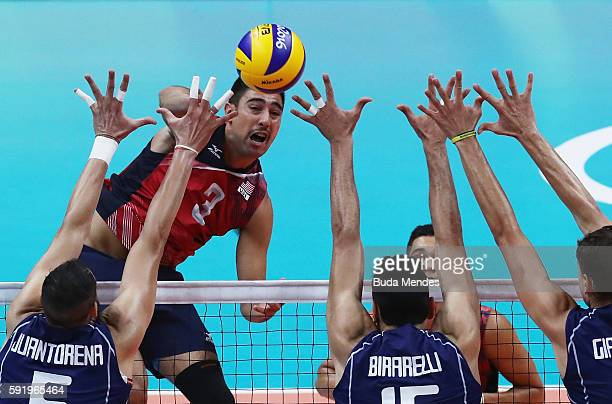 Taylor Sander of United States spikes against the Italy defence during the Men's Volleyball Semifinal match on Day 14 of the Rio 2016 Olympic Games...