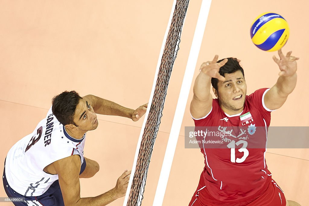 Taylor Sander of USA (left) looks to the ball next to Iran's Mehdi Mahdavi (right) during the FIVB World Championships match between USA and Iran at Cracow Arena on September 2, 2014 in Cracow, Poland.