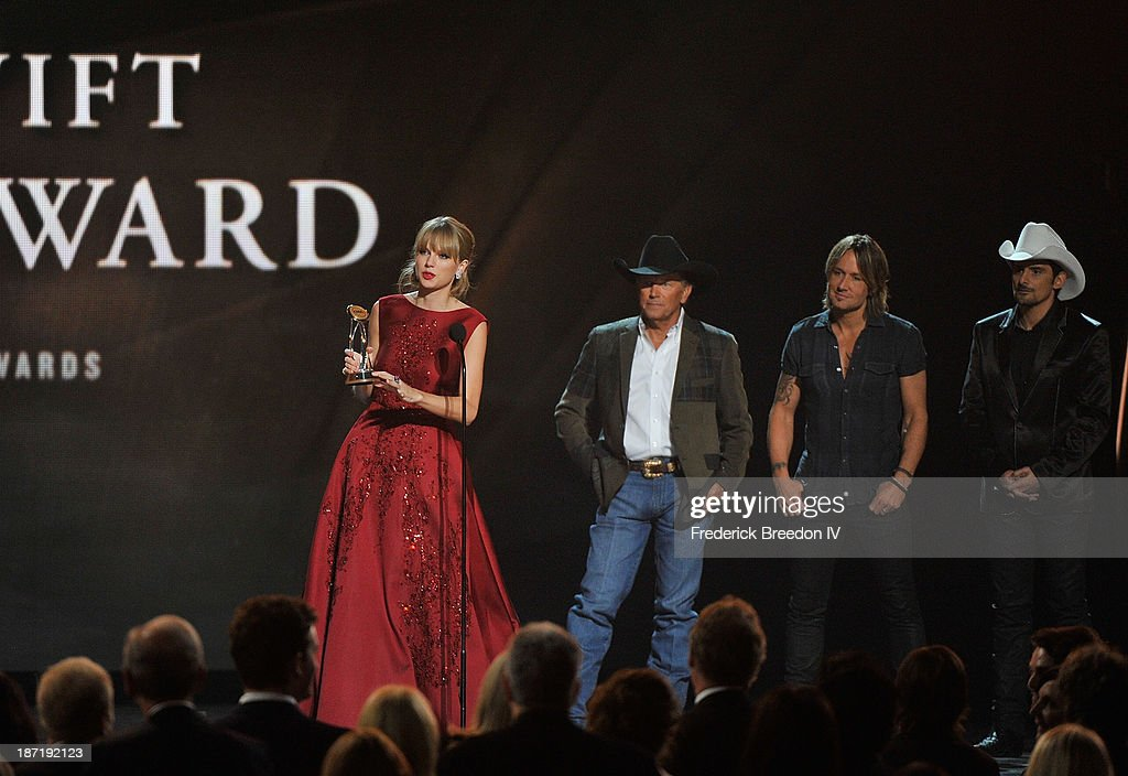 Taylor Swift accepts the Pinnacle Award from (L-R) George Strait, Keith Urban and Brad Paisley during the 47th annual CMA awards at the Bridgestone Arena on November 6, 2013 in Nashville, Tennessee.