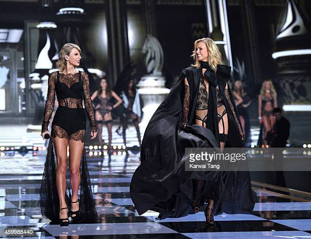 Taylor Swift performs as model Karlie Kloss walks the runway at the annual Victoria's Secret fashion show at Earls Court on December 2 2014 in London...