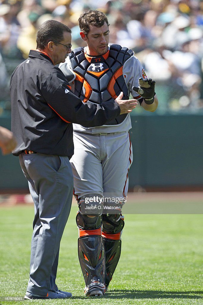 <a gi-track='captionPersonalityLinkClicked' href=/galleries/search?phrase=Taylor+Teagarden&family=editorial&specificpeople=835625 ng-click='$event.stopPropagation()'>Taylor Teagarden</a> #31 of the Baltimore Orioles is attended to by trainer Richie Bancells after dislocating his thumb during the sixth inning against the Oakland Athletics at O.co Coliseum on April 27, 2013 in Oakland, California.