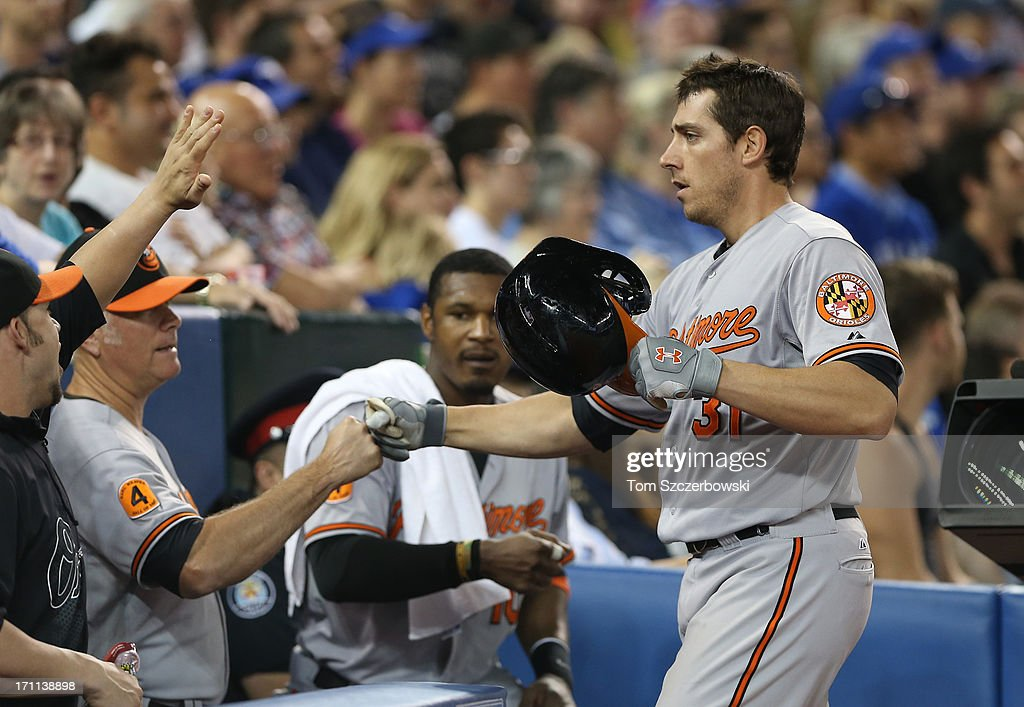 Taylor Teagarden #31 of the Baltimore Orioles is congratulated by teammates after hitting a solo home run in the eighth inning during MLB game action against the Toronto Blue Jays on June 22, 2013 at Rogers Centre in Toronto, Ontario, Canada.