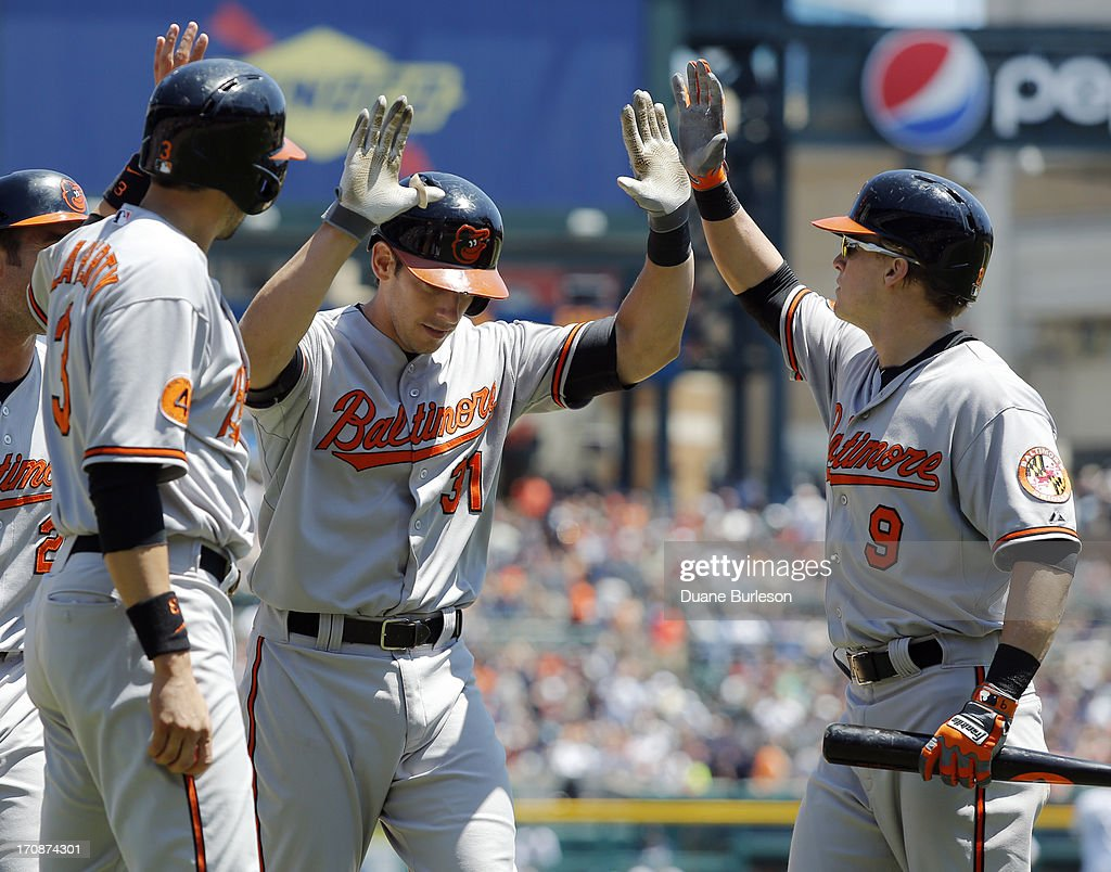 <a gi-track='captionPersonalityLinkClicked' href=/galleries/search?phrase=Taylor+Teagarden&family=editorial&specificpeople=835625 ng-click='$event.stopPropagation()'>Taylor Teagarden</a> #31 of the Baltimore Orioles is congratulated by <a gi-track='captionPersonalityLinkClicked' href=/galleries/search?phrase=Ryan+Flaherty&family=editorial&specificpeople=4412528 ng-click='$event.stopPropagation()'>Ryan Flaherty</a> #3 and <a gi-track='captionPersonalityLinkClicked' href=/galleries/search?phrase=Nate+McLouth&family=editorial&specificpeople=536572 ng-click='$event.stopPropagation()'>Nate McLouth</a> #9 after hitting a three-run home run off of Rick Porcello of the Detroit Tigers in the fourth inning at Comerica Park on June 19, 2013 in Detroit, Michigan. The Orioles defeated the Tigers 13-3.