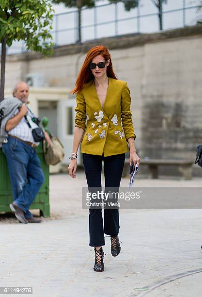 Taylor Tomasi Hill wearing a mustard blazer and flared pants outside Carven on September 29 2016 in Paris France