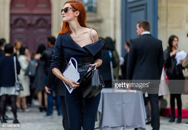 Taylor Tomasi Hill wears a navy ripped off shoulder top outside Dior on September 30 2016 in Paris France